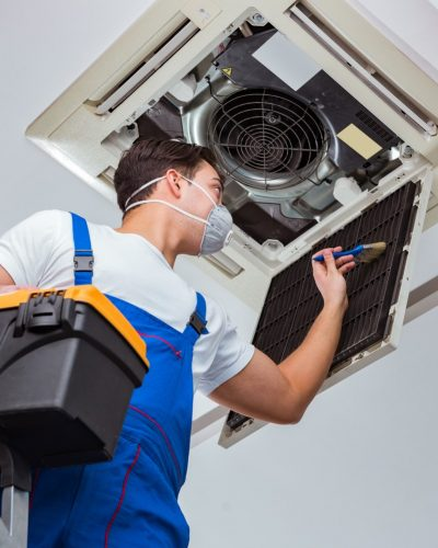 Man with mask repairing ceiling AC unit